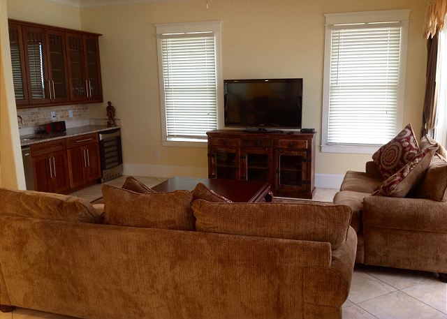 The living room has very comfortable furniture and also features a large flat screen TV, ice maker and wet bar.