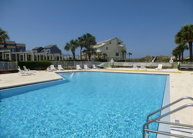 This beachfront unit is steps from the extra large community pool. Sunset Paradise pictured in background.