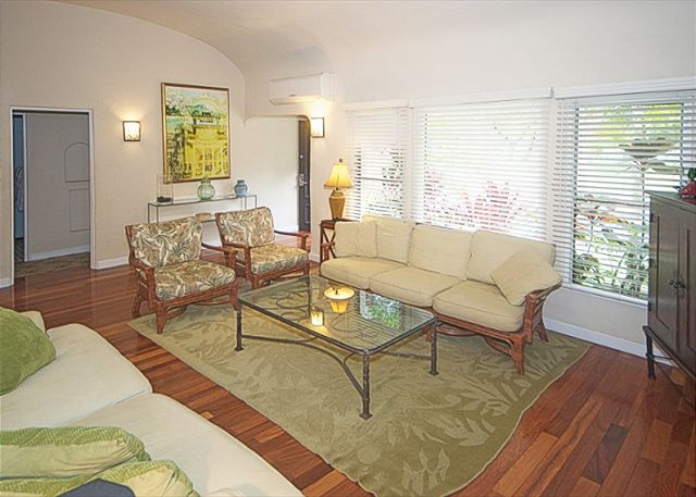 Living room looks onto tropical landscaped yard and beautiful pa