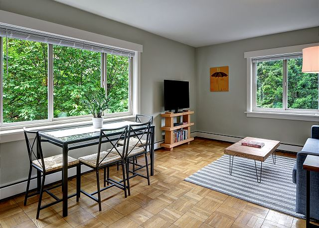 Living/dining table with plenty of greenery outside the windows.