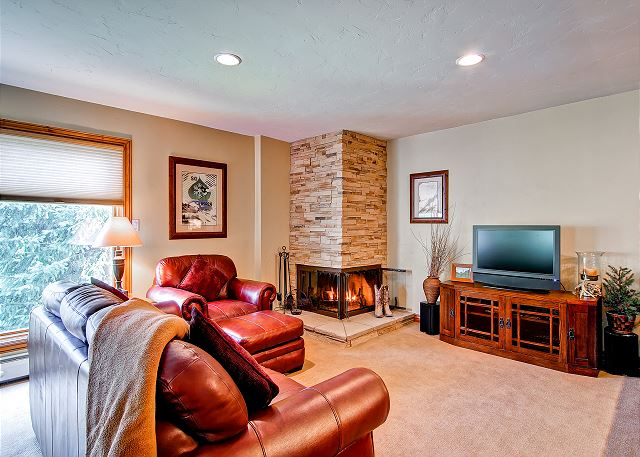 This lovely living room has a wood burning fireplace and flat screen TV