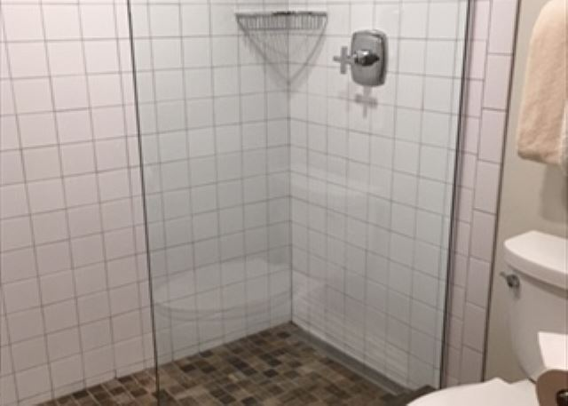 2 bathrooms have glass walk in showers.  1 bathroom has a tub with a shower.