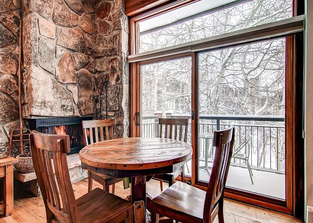A warm gas fireplace with dining room view of creek