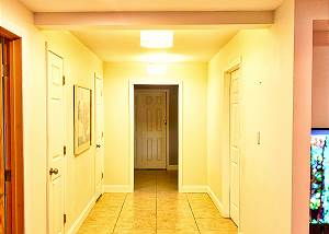 The hallway from the living area to the bunk bedroom glows with ambient lighting, the bath access is halfway down on the right