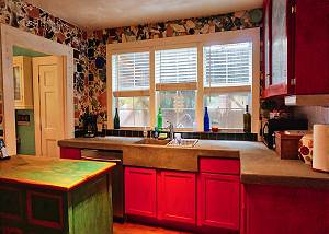 The kitchen has red toned cabinets, double sink, a window with a view and antique wash painted island in a green tone