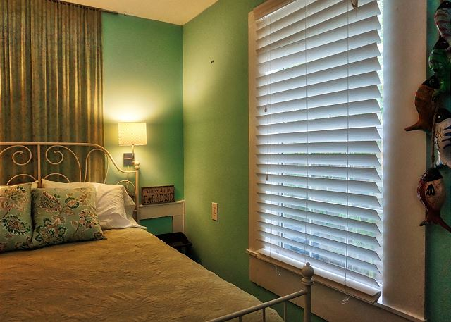 The far side of the bed offers a window that offers natural lighting and a view of the tropical landscaping
