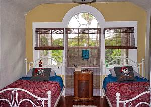 The twin bedroom off of the Master has the most gorgeous set of windows and tropical greenery edging in.