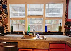 The kitchen sink and counter space located in front of 3 windows that look out to the covered grilling and gathering area.