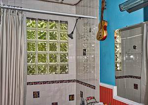 This glass block window in the bathroom offers the hues of foliage from the outdoors landscaping, the bath is tiled and contains hand painted artistic specialty decorative tiles of sea life.