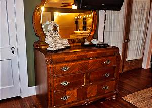 Era piece, antique mirrored dresser sits at the end of the master bed. There is a large flat screen TV hanging above for your entertainment.