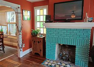 The fireplace is adorned with decorations inside, a large flat screen TV above and colorful glass windows
