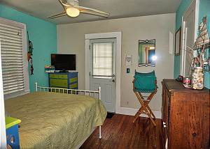 The view as you enter the guest bedroom that also has a door leading to the pool. There is a dresser to the right on the wall and a directors chair in back.