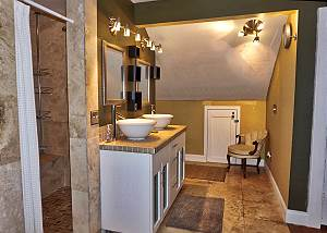 View of the Sinks, shower entry and an alcove at the rear with a chair, this space leads to the restroom facility.