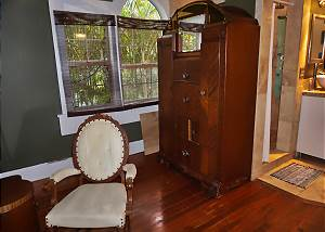 The chair sits in front of the mirrored dressing table, a large antique Armoire behind, this offers a door on each side that opens to a hanging area for clothing and more storage space.
