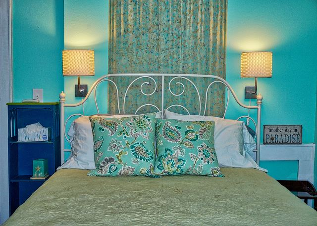 The bed has ambient lighting hanging above and touches of carefully placed beachy art around.