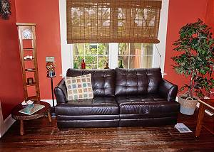 The loveseat in the living room sits in front of a window filled with tropicals outside
