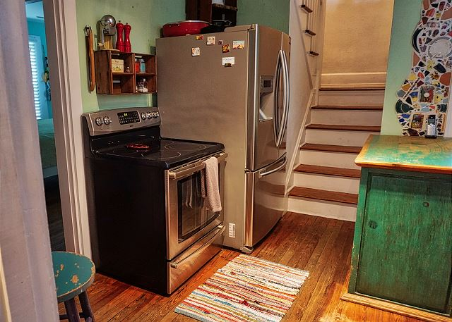 A full size stove and refrigerator sit to the left side as you enter this doorway