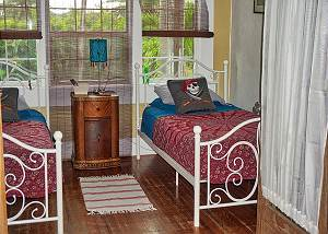 There is a night table between with lighting in the twin bedroom