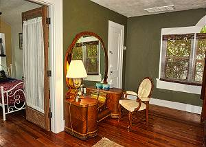 View of the mirrored dressing table and chairs with the door open to the twin bedrooom