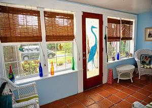 The front entry door offers a beautiful stained glass Egret, once inside the large foyer contains space for visiting and viewing the front landscape along with some storage space.