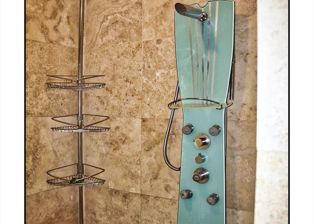 Inside the master bedroom shower, this shower includes a tiled seat that runs the length of the floor