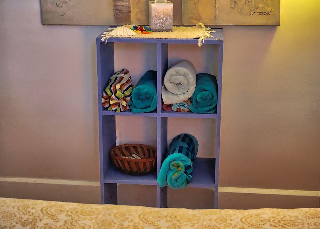 Against the wall is a shelving unit filled with rolled up Pool and Beach towels