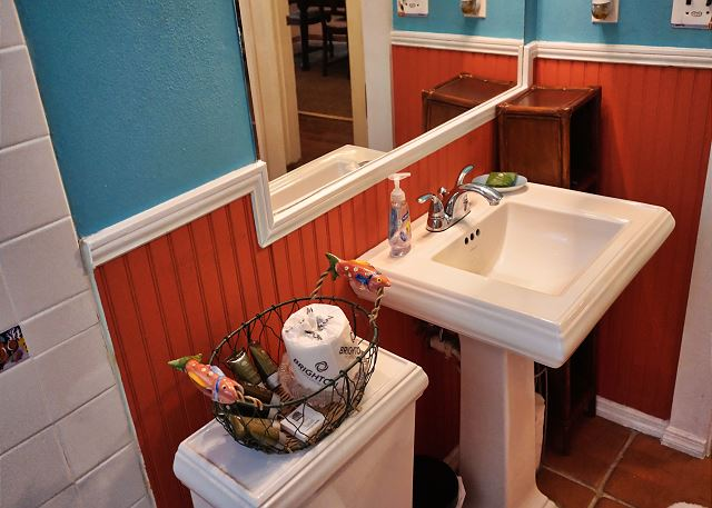 The bath offers a large pedestal sink  and plenty of lighting