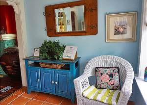 As you enter to your right is seating, a storage piece and an alcove entry to the living room
