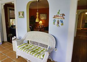 The foyer wicker love seat, situated between the two entrances to the living room