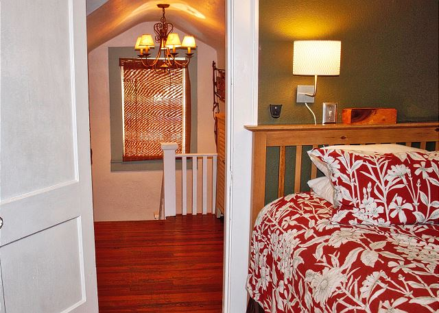 Standing at the foot of the master bed looking towards the entry and upstairs landing leading in or out.
