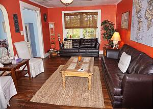 Standing at the fireplace in the living room, the view across, two couches and sitting chairs offer plenty of visiting space. There are original wood floors throughout the home.