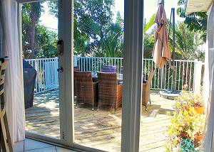 Viewing the outdoor deck on the backside of the home outside the kitchen sliding doors. Theres a grill and a very large umbrella provided to offer shade over the table area