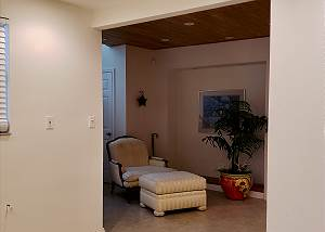 View from the extra room with refrigerator towards the lower sitting room and stairway access