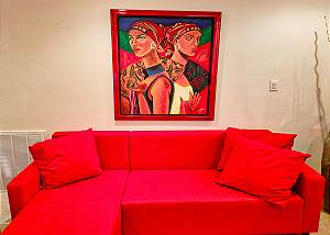 Colorful furniture and artwork along with greenery fill this room