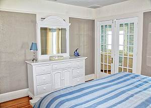 The entry to the west face end upper level bedroom is through these french doors located in the Gulf View sitting room