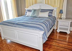 There is a night table with lamp located next to the bed, gorgeous wood floors spread throughout offer a warm and cozy feeling