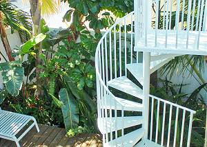 The spiral stairs lead up to the back deck located outside the kitchen. This is where the grill is located and table seating. The lower deck you see contains several lounge chairs.
