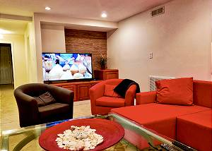 The lower level which is through your entry door upon arrival. It offers plenty of seating and soft ambient lighting, a flat screen TV, two bedrooms, a bath, refrigerator and an immense storage room.