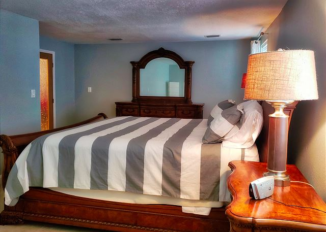 There is a side table on each side of the bed with lamps, this view is standing at the walk in closet entry