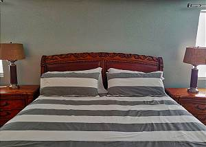 The Master Bed is framed in a heavy wooden sleigh style decor