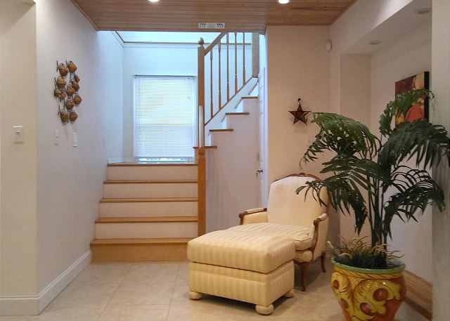 The lower level stair case leading up to the kitchen, second living room, two bedrooms and three balconies