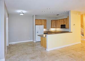 View of the open kitchen and a place for a small dinette or cabinets from the living room