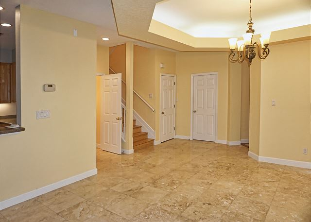 This view shows the entry and dining area, theres a half bath located next to the stairway.