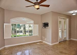 The open living room, dining room and kitchen downstairs, the french doors to the right lead to the screened in back patio.