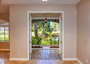 Looking out to the back patio from the kitchen with its many shade trees and often seen Florida Sea Birds. Beyond the pond is a section of the Community Golf Course.