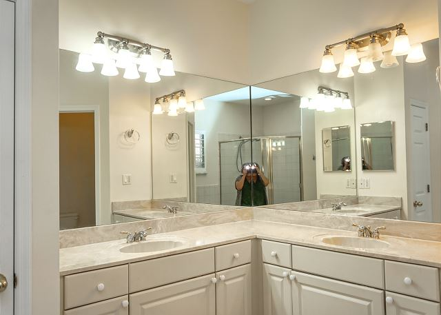 The walls above the vanities are mirrored with separate lighting above each area.