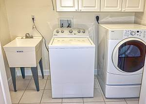 The laundry room is located upstairs across from the shared Guest Bedrooms Bath.