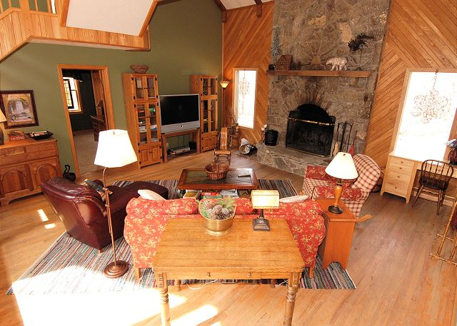 Great room with plenty of seating around a gorgeous stone fireplace and entertainment center with large TV