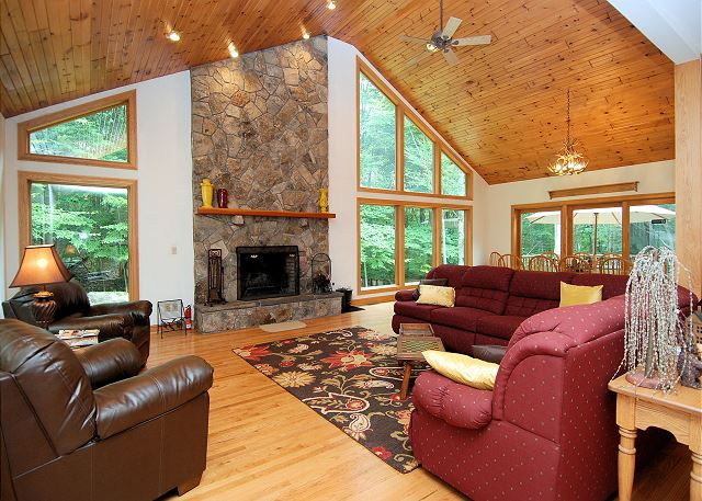The great room has plenty of seating and an amazing wood burning fireplace. Walls filled with windows allow for beautiful nature views and plenty of light.