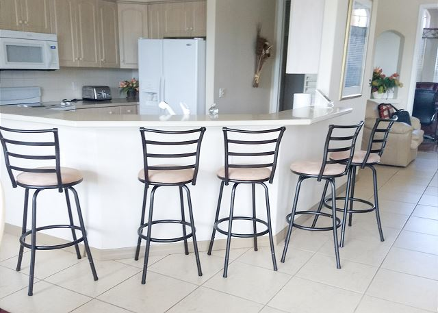 There are five bar stools conveniently located in the kitchen to add additional seating space for guests.